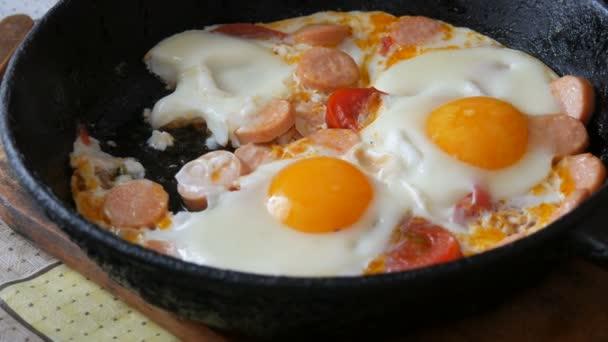 Muž jí vidličkou lahodné čerstvé smažené vejce ve staré litinové pánvi, s kořením, rajčaty, sladkou paprikou a klobásami, s párou. Ranní snídaně v domácí kuchyni