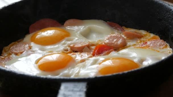 Ízletes, friss tükörtojás öntöttvas serpenyőben, fűszerekkel, paradicsommal, édes paprikával és kolbásszal, gőzzel. Reggeli, kerek tojássárgája az otthoni konyhában