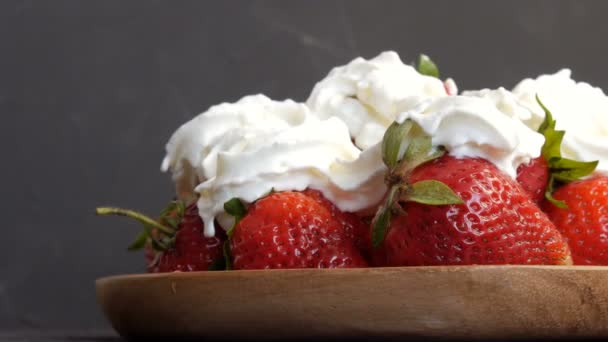 Juicy ripe big red strawberries on an eco bamboo plate on top with whipped cream
