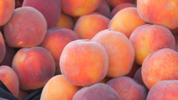Közelkép az érett gyönyörű, friss rózsaszín őszibarack gyümölcsök egy utcai piac pult vagy egy zöldségbolt nyáron.