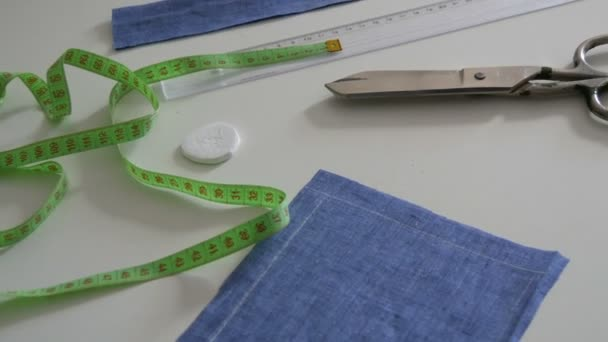 Varrókészlet, olló, kék szövet rongyok, centiméter fehér asztal háttér. Varróműhely, játékgyári munkafolyamat