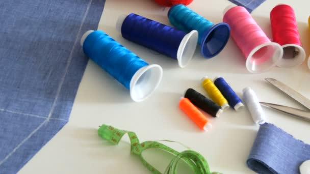 Nähset, Nähschere, Spulen mit Faden, Nadelkissen mit Nadeln, Zentimeter auf weißem Tischhintergrund. Nähwerkstatt, Spielzeugfabrik