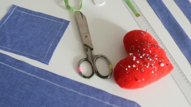 Varrókészlet, olló, kék szövet maradványai, egy piros tűpárna tűvel, szív alakban, egy centiméter fehér asztal háttér. Varróműhely, játékgyári munkafolyamat