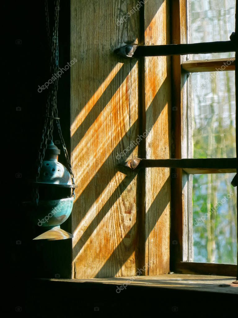 Lamp hanging at the wooden window with bars.