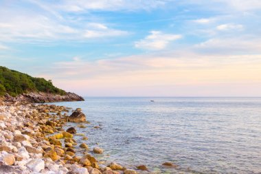 Adriatic sea coastline with stoned shore in Montenegro, awesome landscape at sunset time, gorgeous seascape.