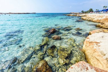Daylight view to Nissi Beach with colorful bright blue rocky water and sky with clouds. Negative copy space, place for text. Ayia Napa, Cyprus