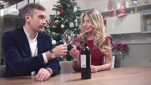 White caucasian young couple at a romantic christmas dinner. Man speaking about wine. Red dress, holiday decorations and gifts.
