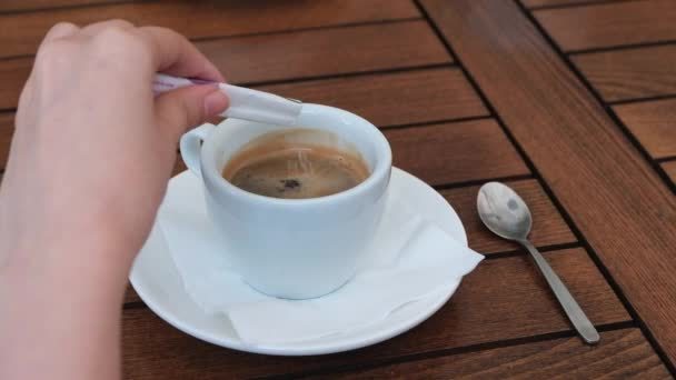 Woman adding sugar to black coffee at a restaurant table