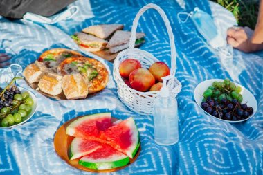 Picnic blanket with goodies and disinfectant, in a park during the pandemic in Chisinau, Moldova