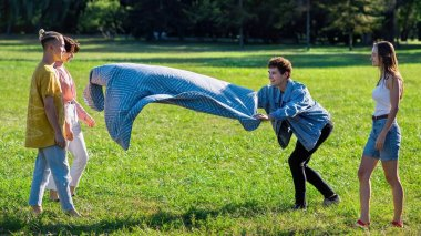 Group of friends spread a picnic blanket in a park during the pandemic in Chisinau, Moldova