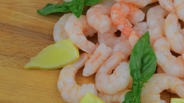 Cooked and peeled prawns with slices of lemon and leaves of basil on chopping board. Food video. Healthy food. Bio recipe
