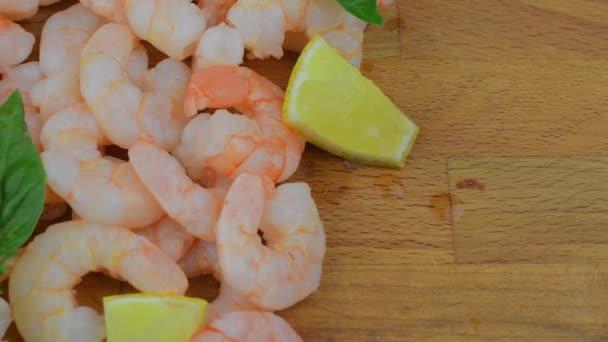 Vařené a oloupané krevety s plátky citronu a lístky bazalky na prkénko. Potravin video. Zdravé jídlo. Bio recept