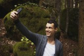 Man takes a picture on mobile phone in the pine forest on a cold sammer day