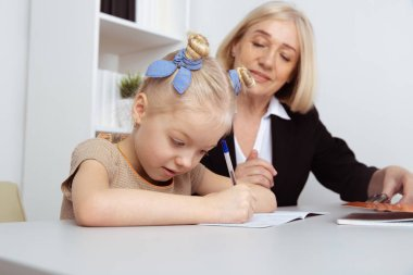 Picture of female tutor helping little girl. Teacher and pupil concept.