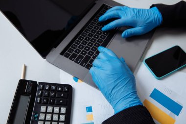Cropped shot of of worker in protective gloves while working with laptop in office. Healthcare concept