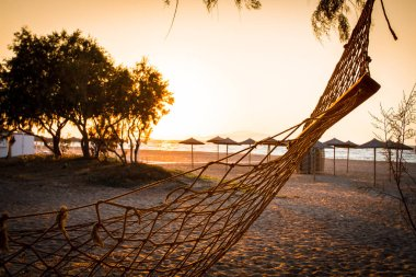 Beach and sea view with empty hammock sunshades at sunset chillout