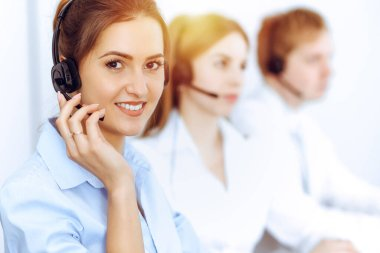 Call center operators. Focus on beautiful business woman using headset in sunny office