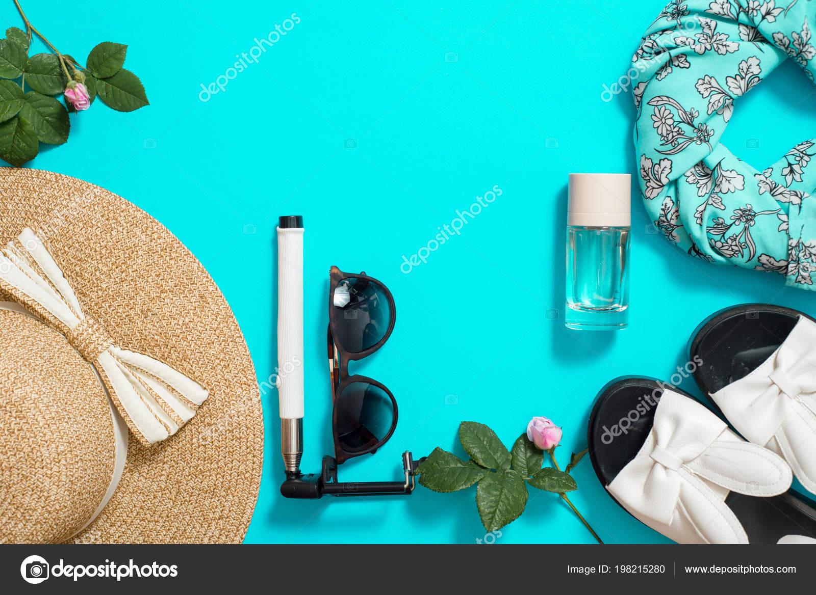 6f8a5a02ae Accesorios de verano de la vista superior, sombrero de paja, gafas de sol,  flores y selfie palillo sobre un fondo azul. Fin de semana y salir.