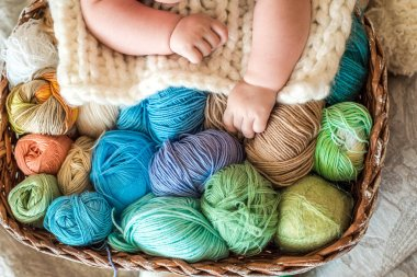A cute baby lies on a basket with tangles of knitting threads. Hendmeid of multi-colored threads. Children's hands