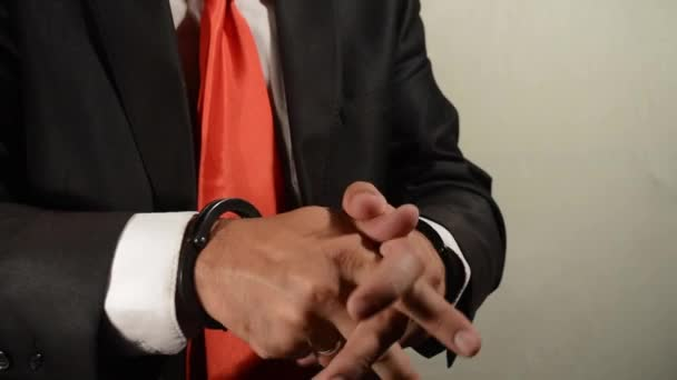 The businessman in handcuffs is allowed to make a phone call