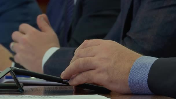 At a meeting of businessmen, a man prints on a tablet, conducts a dialogue and makes corporate decisions, close - up of hands