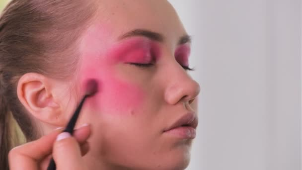 Eye makeup artist applying and feathering eyeshadow powder. Beautiful woman model face. Close-up.