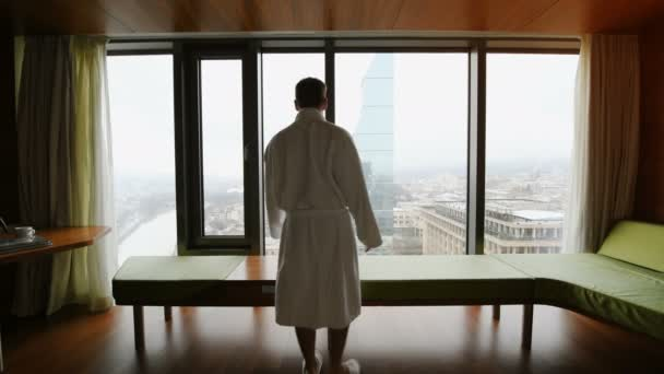Handsome Man wearing bathrobe doing morning stretching exercising in Living Room at apartments with great city view.
