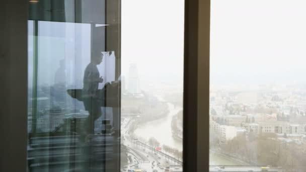 Reflexe člověka chůze na běžeckém pásu v posilovně ve vyšším patře s výhledem na město se automobilové dopravy komunikacích