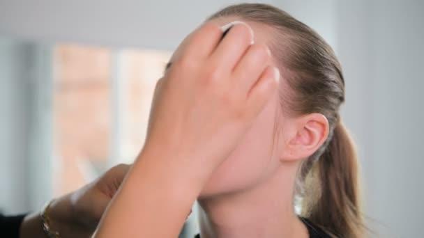 K nepoznání vizážistka použití kapaliny nadace na mladých ženách tvář pomocí houbičky. Profesionální make-up v salonu. Nahé líčení