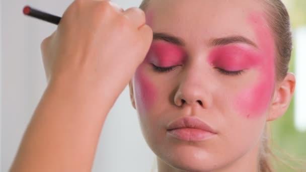 Modelka připravuje na natáčení. Make-up artist ruce používat kosmetiku na plochu modelu