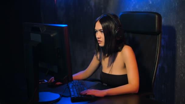 Seriózní žena hráče hrát online hru na pc počítač nosit sluchátka a povídání s tým pomocí mikrofonu