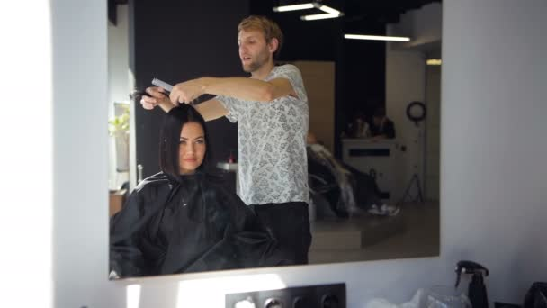 Male professional hairdresser is straightening brunette womans hair using a hairstraightener in hair salon
