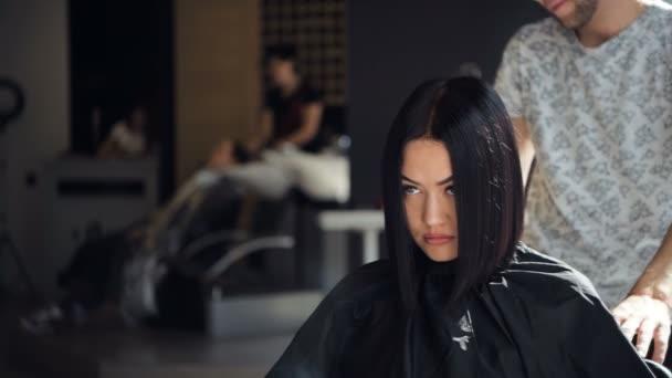 Mladí profesionální hip mužský kadeřník řezání tmavé vlasy ženy klienta v salonu