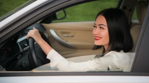 Porträt einer hübschen, glücklichen Frau, die im Auto vor der Kamera flirtet. Gespräch mit einem anderen Autofahrer im Stau.