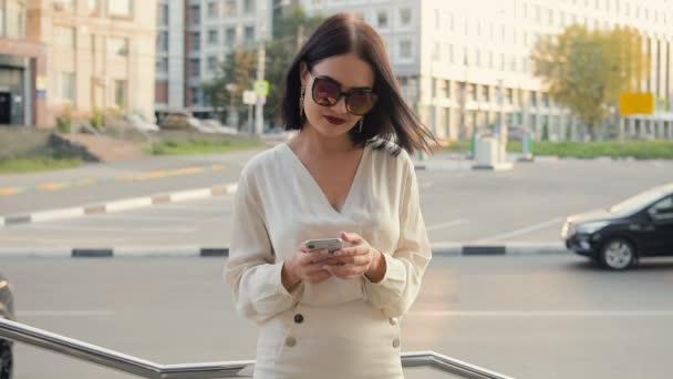 Krásná žena pomocí aplikace technologie smart phone v ulicích města, městský životní styl šťastný. Zpomalený pohyb