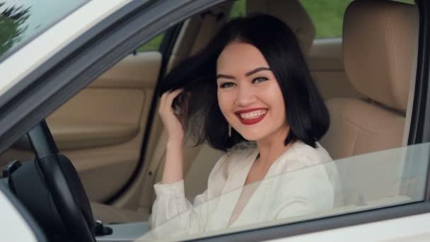 Porträt einer hübschen, glücklichen Frau, die im Auto vor der Kamera flirtet. Gespräche mit einem anderen Autofahrer im Stau. Zeitlupe.
