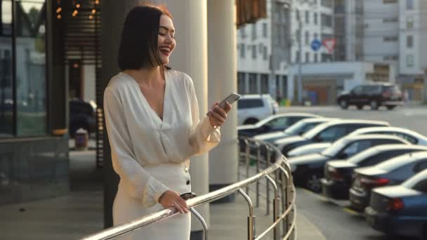 Beautiful elegant business woman walking through city connected using smart phone. Happy lady wearing white blouse and skirt messaging or browsing social networks on her smart phone outdoors in slow