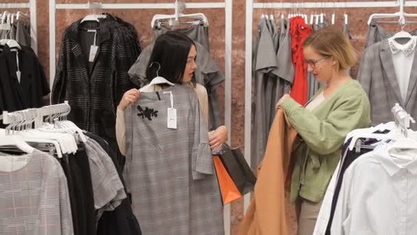 Young woman chooses a dress in a clothing store and consults with her friend. Trying on dresses in the mirror. Girl brunette is going to buy a dress and consults with blonde friend.