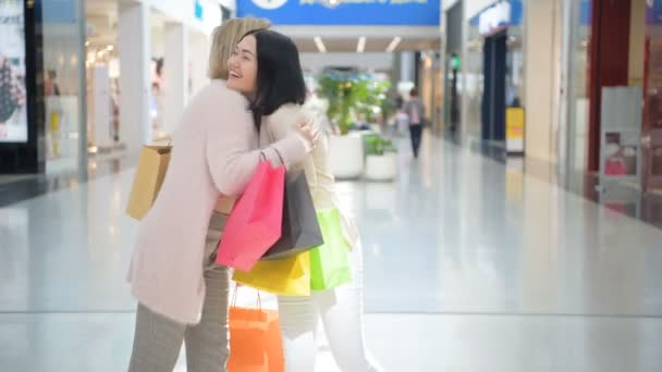 Two girls walking with shopping bags indoors is hugging each other in shopping mall.