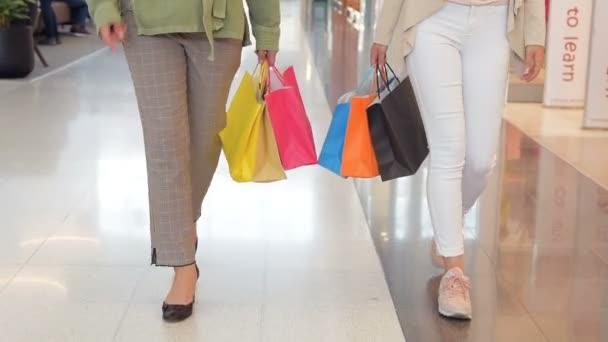 Ženské nakupující chodit na nákupní centrum s prodejem tašek v pomalém pohybu. Detail ženy zákazníků držet papírový sáček s nákupy. Pohled zepředu