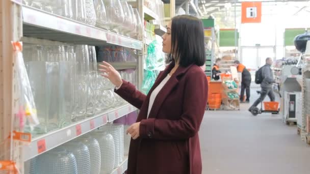 Young girl chooses glass vase in the section of dishware in the  hypermarket. Customer shopping in housewares store buying kitchen goods.  Slow motion