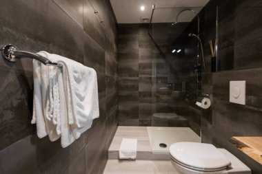 Modern private bathroom interior. Towels on a hanger