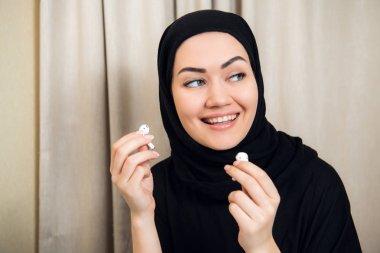 An arabian woman using modern wireless earphones to listen music. She rests at home.