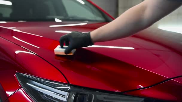 Detaily vozu - Muž nanáší nanoochranný povlak nebo vosk na červený automobil. Krycí kapota vozu s tekutým leštidlem na sklo.