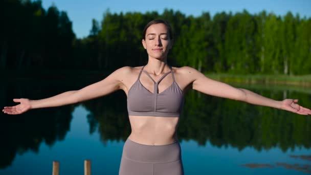 Egy fiatal nő, aki napnyugtakor a tónál pihen, árt a kinyújtózkodásnak. Csinállak reggel az erdei tónál..