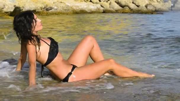 Egy gyönyörű fiatal nő ül a falon, közvetlenül a tengerparton található egy fürdőruhát és a napsütésben, míg a hullámok óvatosan fröccsenő.