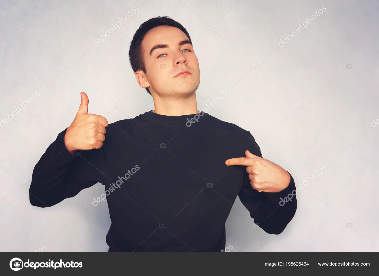 c7ce107d51e73 Atractivo joven en camiseta blanca apuntando con su dedo sobre fondo azul.  chico en una camiseta negra señala un dedo a sí mismo con el otro en la  parte ...