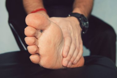 Man's hand being massaged a foot. Man with painful and inflamed gout on his foot around the big toe area.