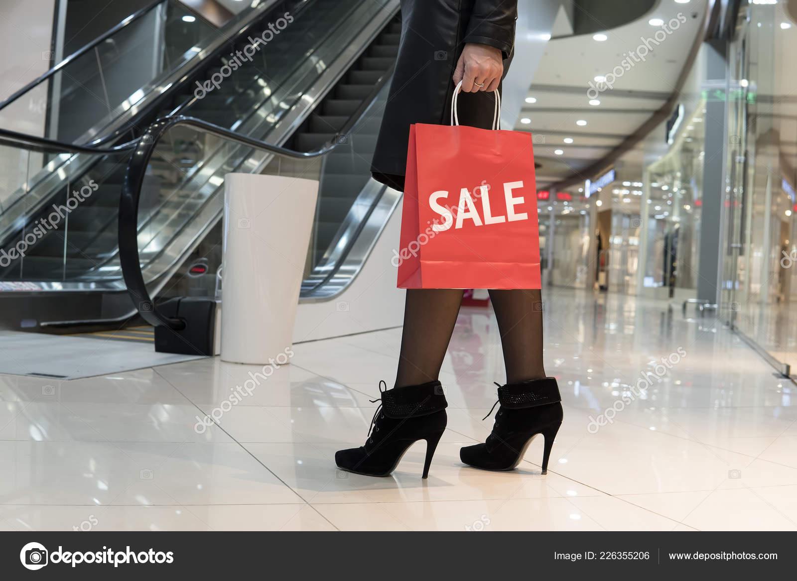 73b7c1e5c Menina na moda elegante jovem vai a uma loja de roupas grande com sacolas  de compras. A venda de inscrição no saco vermelho. Compras durante as vendas .