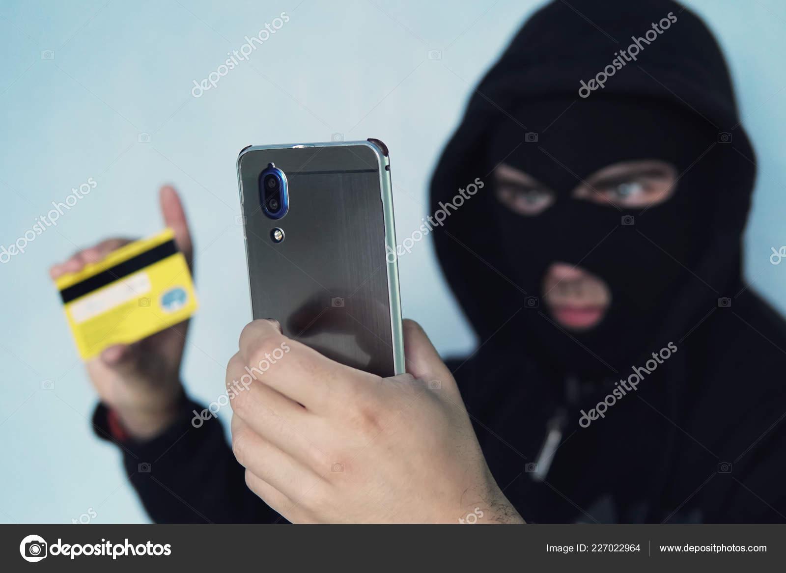 Carte Bancaire Sur Telephone.L Escroc Voleur Tient Un Telephone Portable Et Une Carte De Credit